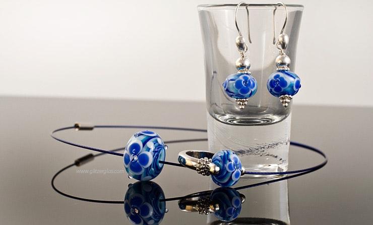 """Ensemble """"Meeresblüte 2"""", bestehend aus 1 Fingerring, 2 Ohrhänger und Halsreif mit blauen Murano-Glasperlen."""