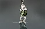 Frosch-Kettenanhänger mit olivgrüner Glasperle. Der Glasschmuck ist mit versilbertem Frosch und Muranoglas-Perle.