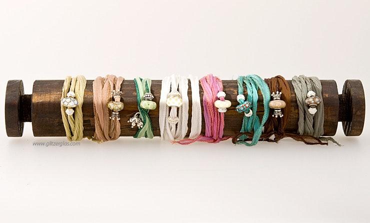 Farbvarianten von indischen Seidenarmbändern mit passenden Glasperlen und echt Silber Schmuckteilen