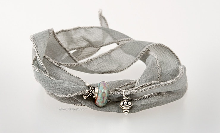 Mausgraues indisches Armband aus Seide mit einer Modulperle und zwei Echtsilber925 Schmuckstücken.(verkauft)