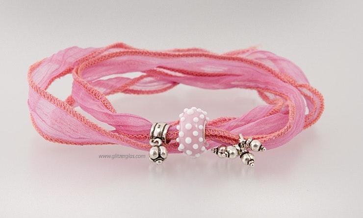 Rosa Glasperle in Pandora- und Trollbeadstyle an rosaroten Seidenband. Mit Echtsilberschmuck 925 bestückt. CHF 58.-